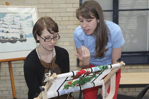 SPUN member Michelle Patnick teaches a volunteer how to needlepoint at the Philadelphia Museum of Art.  Photo credit:  Andrea Nunez